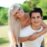 Cute couple piggybacking outdoors. — Stock Photo #22237641