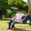 Foto Stock: Cute young couple relaxing on bench.