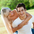 Handsome couple piggybacking in park. — Stock Photo