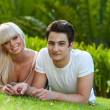 Portrait of young couple laying on green grass. — Stock Photo
