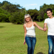 Young couple hopping together in park. - Stock Photo