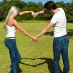 jong koppel maken liefde teken met armen — Stockfoto