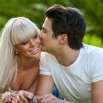 Young man kissing girlfriend on cheek. — Stock Photo #22238037