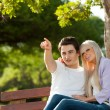 Young man indicating something to girlfriend. — Stock Photo