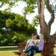 Foto Stock: Young couple sitting on bench in park.