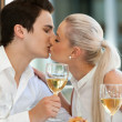 Cute couple kissing at dinner table. — Stock Photo