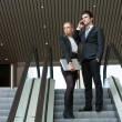 Young business couple on escalator. - Stock Photo
