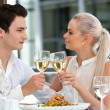 Attractive couple making a toast at dinner. — Stock Photo