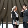 Stock Photo: Business couple talking on phone in mall.