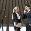 Business couple talking on phone in mall. - Stock Photo