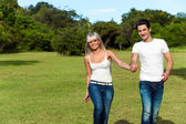 Young couple hopping together in park. — Stock Photo