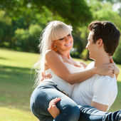 Young man carrying girlfriend in arms. — Stock Photo