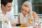 Cute couple looking at smart phone at dinner. — Stock Photo