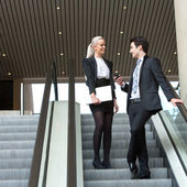 Business couple talking on escalator. — Stock Photo