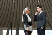 Business couple talking on phone in mall. — Stock Photo