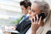 Businesswoman talking on smart phone at meeting. — Stock Photo