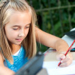 Stock Photo: Cute girl doing schoolwork outdoors.