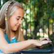Cute girl typing on laptop outdoors. — Stock Photo