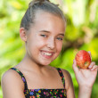 Stock Photo: Cute girl holding red apple outdoors.