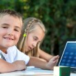 Stock Photo: Boy showing homework on tablet outdoors.