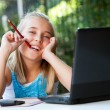 Foto Stock: Cute girl with pencil in mouth at desk.