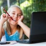 linda garota com lápis na boca na mesa — Foto Stock