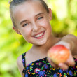 Cute healthy girl offering red apple. — Stock Photo