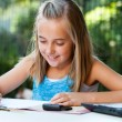 Young girl doing schoolwork with pencil outdoors. — Stok fotoğraf