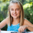 Portrait of cute girl doing homework outdoors. — Stok fotoğraf