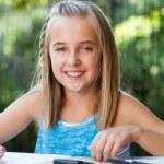 Portrait of cute girl doing homework outdoors. — Stock Photo
