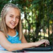 Cute girl doing homework on laptop outdoors. — Stok fotoğraf