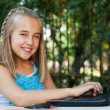 Cute girl doing homework on laptop outdoors. — Lizenzfreies Foto