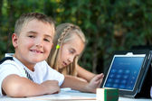 Boy showing homework on tablet outdoors. — Stockfoto