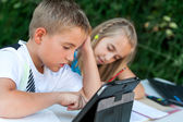 Children doing homework ourdoors. — Stock Photo
