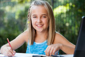 Portrait of cute girl doing homework outdoors. — Stock Photo