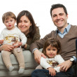 Stock Photo: Young parents with kids on couch.