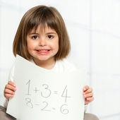 Leuk meisje math bedragen tonen op papier. — Stockfoto