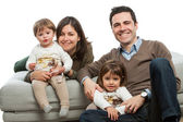 Jonge ouders met kinderen op bank. — Stockfoto