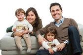 Młodzi rodzice z dziećmi na kanapie. — Zdjęcie stockowe