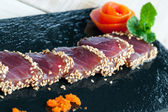 Japanese tataki served on black tile. — Stock Photo
