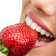 Extreme close up of teeth biting strawberry. — Stock Photo #24722879
