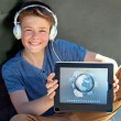 Stock Photo: Cute boy showing tablet with multimedia symbols.
