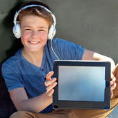 Cute boy with earphones showing blank tablet screen. — Stock Photo