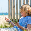 Boy sitting nex to wooden fence on beach. — Stock Photo #25930729
