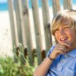 Cute boy relaxing next to wooden fence. — Stock Photo #25930735