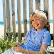 Happy boy sitting next to fence on beach. — Stock Photo #25930757
