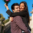 Stock Photo: Girl embracing boyfriend with flowers in hand.