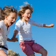 Shouting kids having fun jumping. — Stock Photo