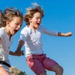 Shouting kids having fun jumping. — Stock Photo