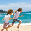 Two boys running on beach. — Stock Photo